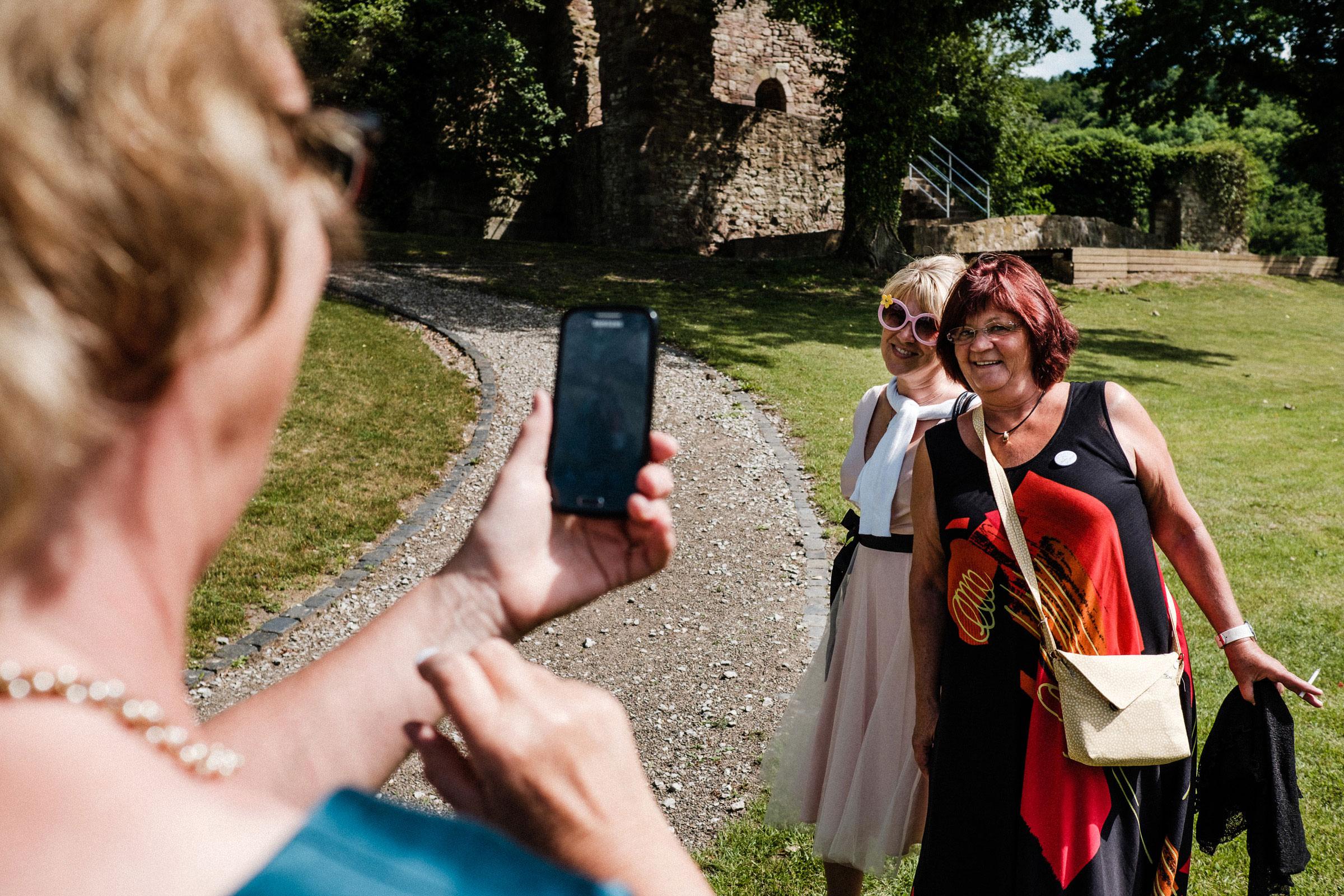 Hochzeitsgäste fotografieren sich gegenseitig auf der Hochzeit