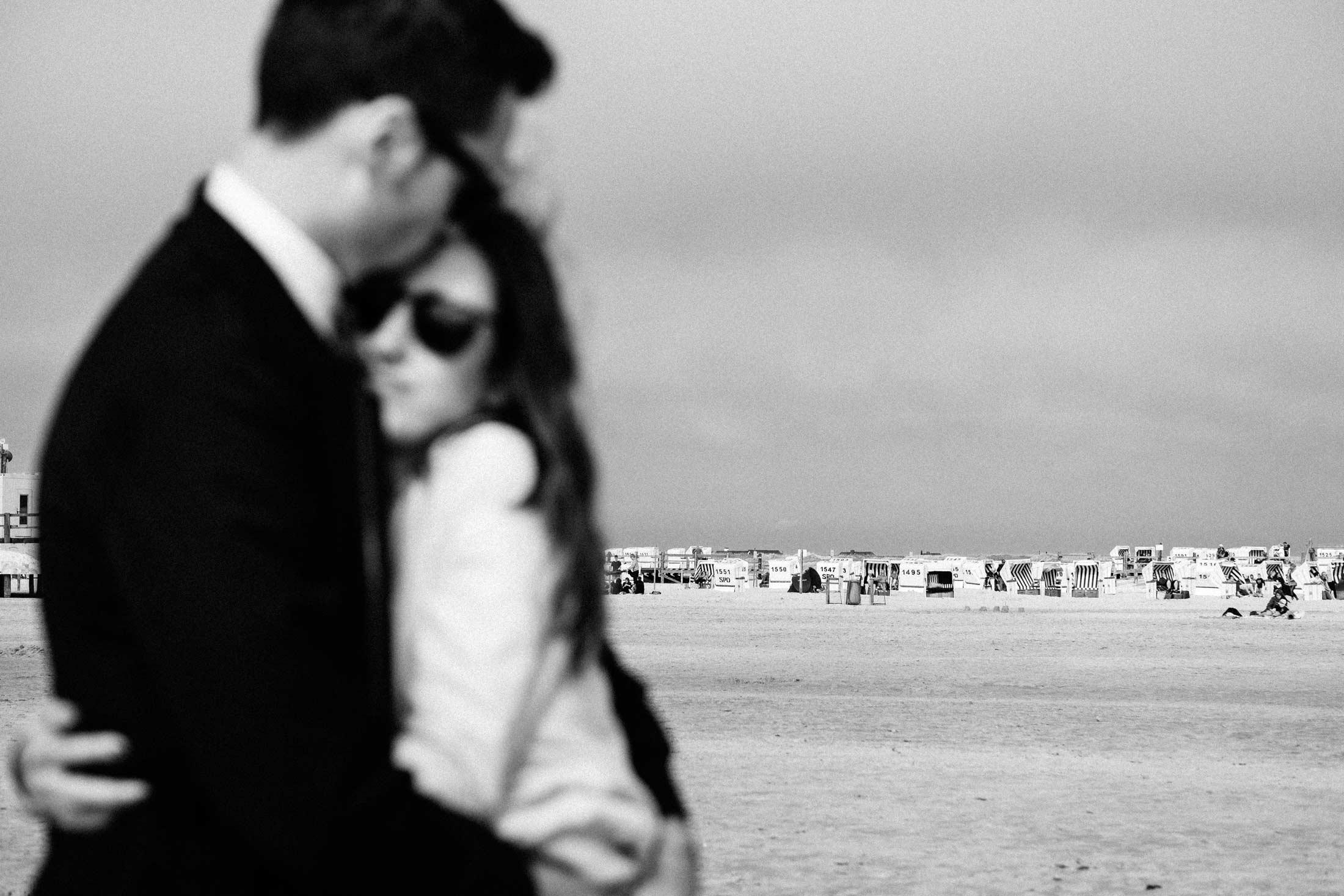 Hochzeitspaar am Strand von St. Peter-Ording mit Strandkörben im Hintergrund
