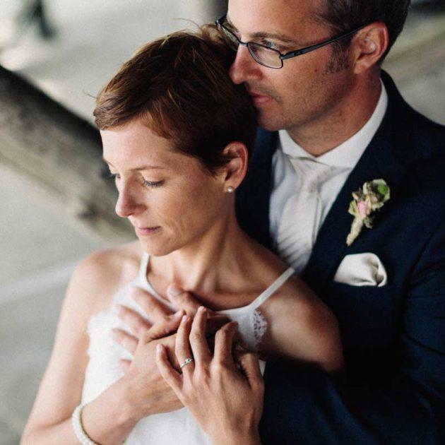 Eine romantische Umarmung des Hochzeitspaares unterhalb der Pfahlbauten in St. Peter-Ording