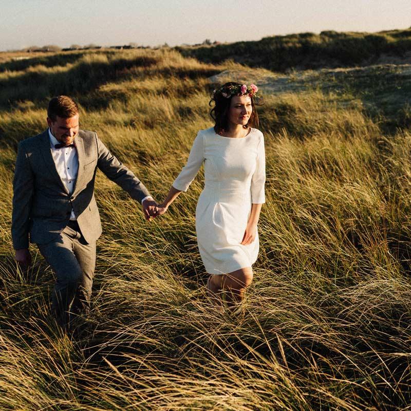 Brautpaar läuft durch die Dünen von St. Peter-Ording am Tag ihrer Hochzeit